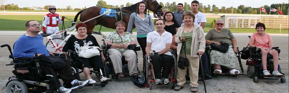 Group of people, some in wheelchairs, posing for a picture in front of the Grand River Raceway with a horse and jockey.